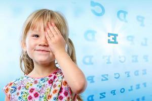 liten flicka läser ögon diagram. foto