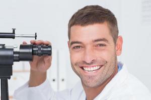 glad optiker som använder spaltlampa i kliniken foto