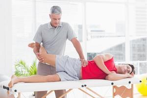 fysioterapeut som gör benmassage till sin patient foto