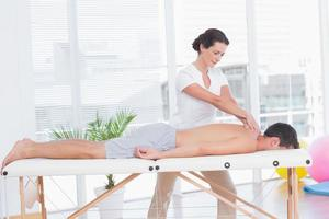 fysioterapeut som gör nackmassage foto