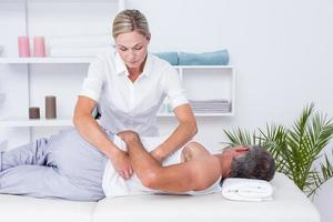fysioterapeut som gör axelmassage till sin patient foto