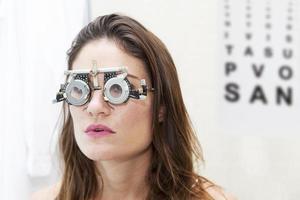 vacker kvinna testar nya hjälplinser med phoropter foto
