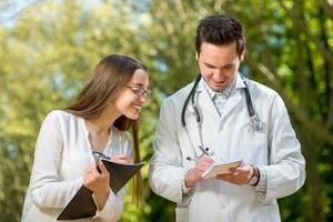 läkare med ung och vacker assistent som talar i parken. foto
