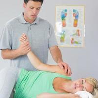 stilig fysioterapeut som behandlar patientens arm foto