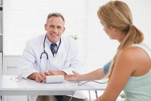 leende läkare tar patientens blodtryck foto
