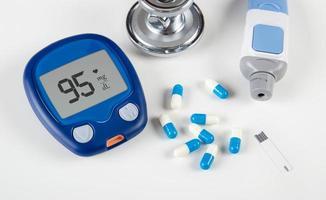 diabetisk testkit och stetoskop på vit bakgrund