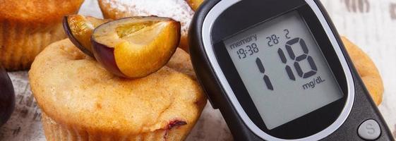 glukometer och muffins med plommon på träbakgrund, diabetes foto
