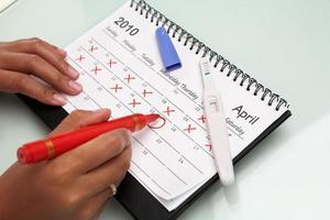 hand cricling kalender med graviditetstest foto