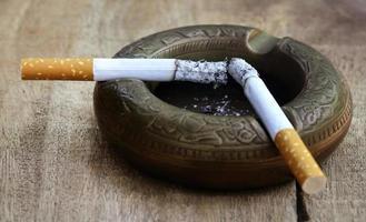 brinnande cigarett på en gammal askfat foto