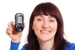 le kvinna med glukosmätare på vit bakgrund foto
