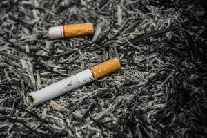 cigarett i aska bränner liv och naturbakgrund foto