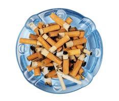 cigarettstumpar i askfat isolerad på vitt foto