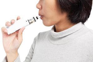 asiatisk kvinna andas in från en elektronisk cigarett. foto