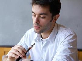 ung man röker elektrisk cigarett foto