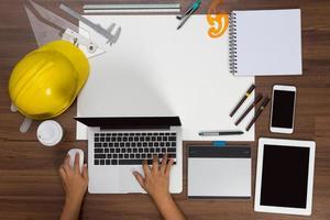 kontorsskrivbord bakgrund hand med ett bärbar dator byggprojekt foto