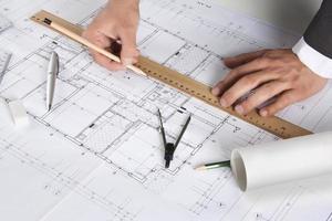 arkitekt som arbetar med arkitektoniska planer foto