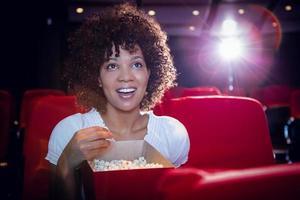leende ung kvinna tittar på en film foto