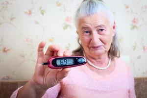kvinna testar för högt blodsocker foto