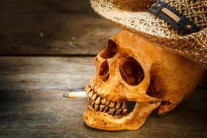 skalle med cigarett, stilleben. foto