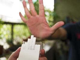 vägrar cigaretter med ett handtecken foto