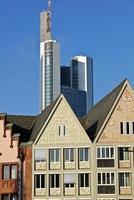 Frankfurts historiska gamla stadsbyggnader kontrasterar med en modern skyskrapa. foto