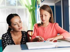 mamma som hjälper dotter med läxor foto