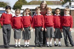 grundskoleelever med lärare på lekplats foto