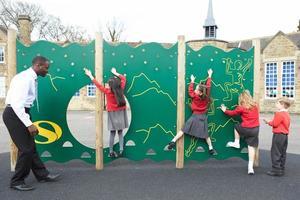 barn på klättringväggen i skolan lekplats vid brottid foto