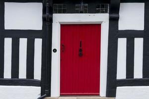 röd ytterdörr i ett timmer inramat tudorhus foto