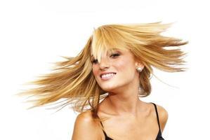 vacker blond kvinna som skakar håret foto