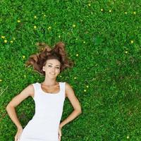 ung kvinna i vit klänning liggande på gräset foto