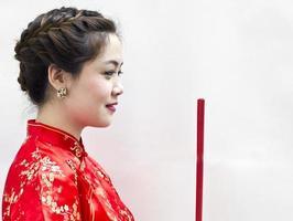 kinesisk ung kvinna med traditionskläder som håller josspinnar ( foto