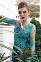 vacker kvinna med elegant frisyr i lyxig silkeklänning foto