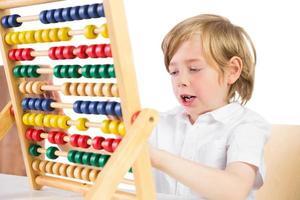 student som gör matematik på abacus foto