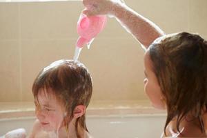 två flickor som delar bubbelbad och tvättar hår foto
