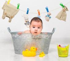 baby flicka badar i ett tråg foto