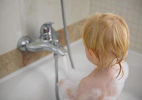 barntvätt i skumt badkar foto