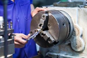 fräsmaskinoperatör som arbetar i fabriksverkstad foto
