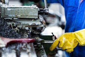 arbetare som driver borrmaskin i fabriken foto