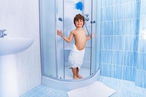 glad liten pojke i hotellets dusch foto