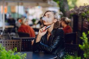 vacker glamorös brunett röker elektronisk cigarett foto