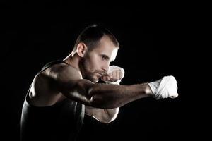 muskulös man, knyta ett elastiskt bandage på handen, svart foto