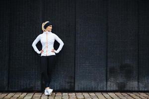 bestämd kvinna vilar efter jogging i staden foto