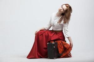 kvinna sitter på resväska, isolerad, vit bakgrund foto