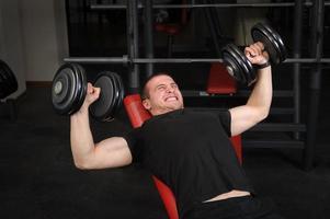 ung man gör hantel lutning bänkpress träning i gymmet foto