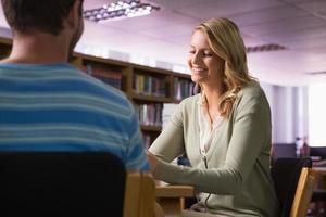 student får hjälp av handledare i biblioteket foto