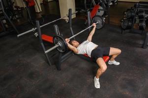 ung man gör bänkpress träning i gymmet