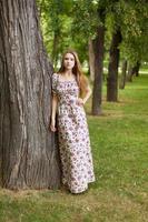 vacker ung kvinna ler i parken foto