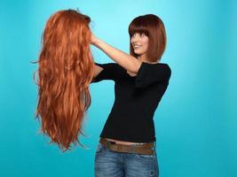 vacker kvinna som beundrar peruk med långt hår foto