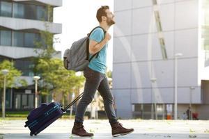 ung man går med resväska och väska foto